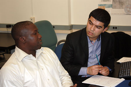 Two students confer at the vulnerability mapping workshop.