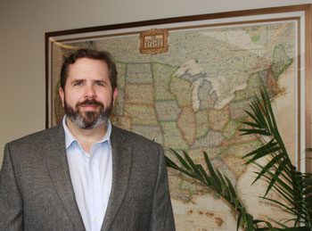 Greg Yetman standing in front of a map.